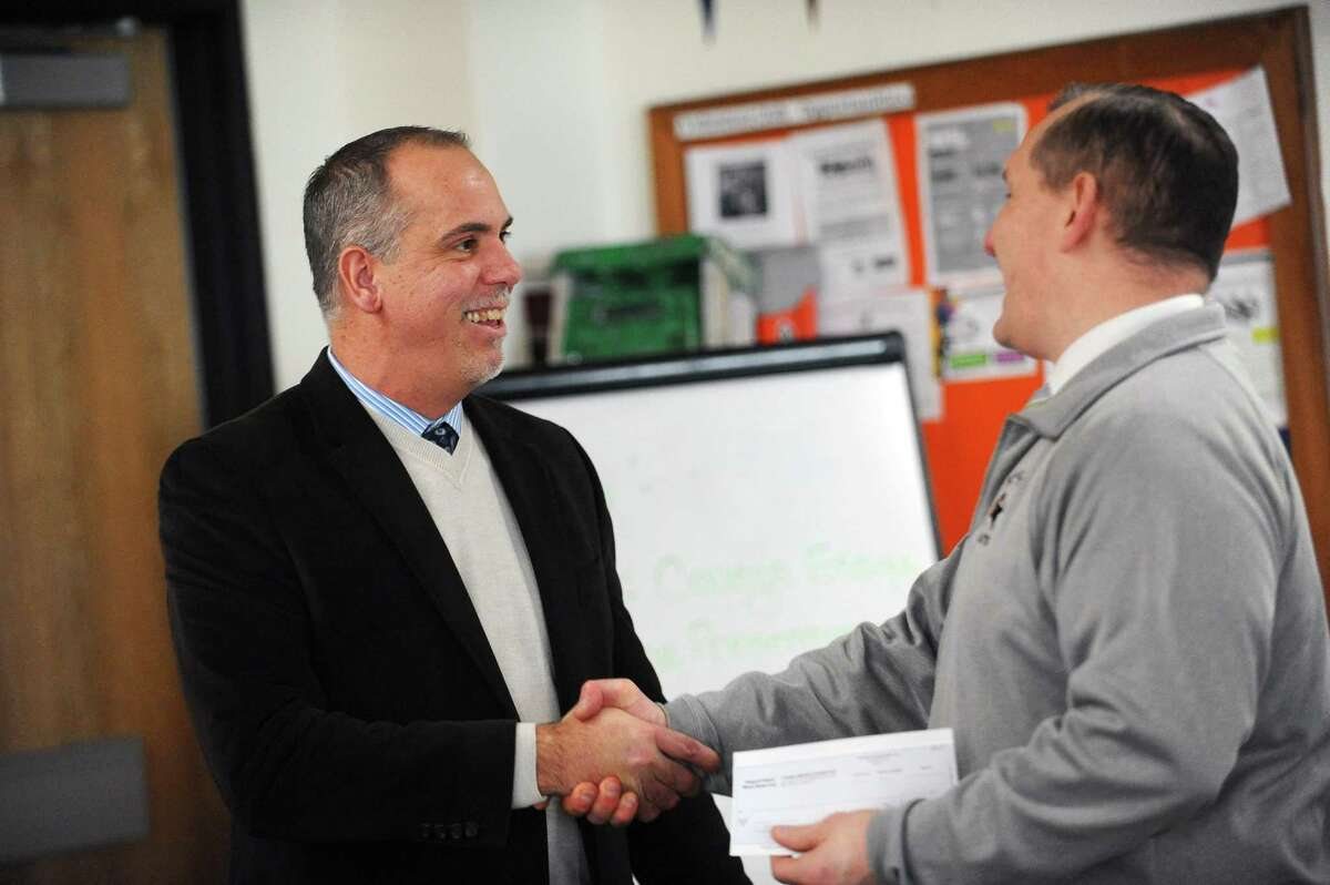 Stamford High principal Raymond Manka and Toshiba senior manager Eddie Temistokle shake hands and exchange a $4,000 grant check inside the College and Career Center at Stamford High School in downtown Stamford, Conn. on Tuesday, Feb. 13, 2018. Stamford High students won a $4,000 grant from the Toshiba America Foundation for 13students to participate in the Student Spaceflight Experiment Program and will use the money to purchase a bioreactor used to simulate a low gravity environment. Their experiment will launch into space in June and land at the International Space Station.