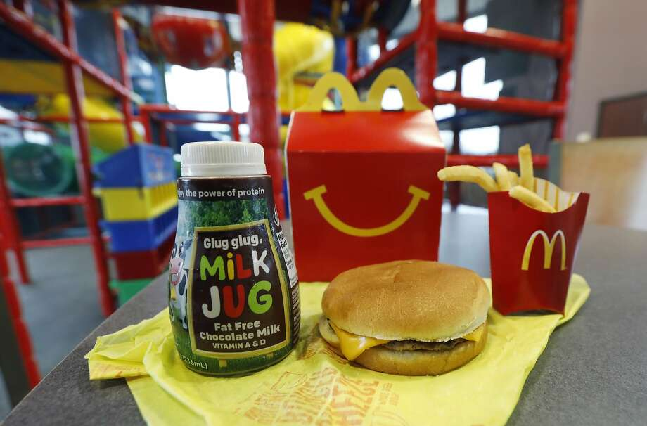 A Happy Meal featuring non-fat chocolate milk and a cheeseburger with fries, are arranged for a photo at a McDonald's restaurant in Brandon, Miss., Wednesday, Feb. 14, 2018. McDonald's will soon banish cheeseburgers and chocolate milk from its Happy Meal menu. Diners can still ask specifically for cheeseburgers or chocolate milk with the kid's meal, but the fast-food company said that not listing them will reduce how often they're ordered. (AP Photo/Rogelio V. Solis) Photo: Rogelio V. Solis, Associated Press