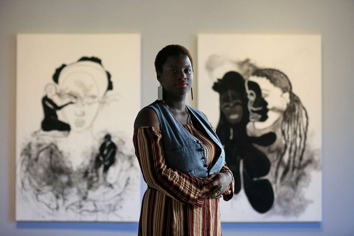 Kenyatta A.C. Hinkle stands for a portrait in front of The Evanesced: Rivers (left) and The Evanesced: Sojourn (right) at the San Francisco Art Commission main gallery on Wednesday, February 7, 2018 in San Francisco, Calif. Hinckle's solo exhibition, The Retrieval, will run from February 16 through April 7.