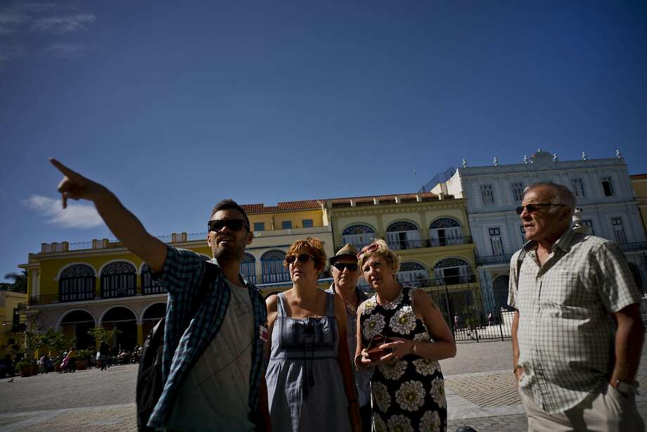 Private tour guide Javier Rodriguez (left) speaks with tourists in Havana. Figures from the Cuban government show that 2017 was a record year for tourism, with 4.7 million visitors. Photo: Ramon Espinosa, Associated Press