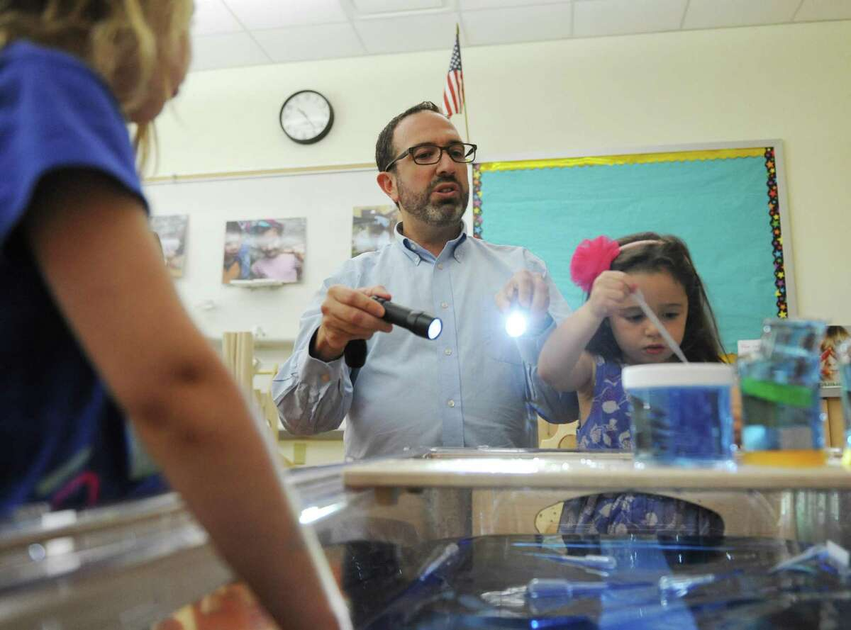 Nursery School Director David Cohen gives children flashlights to explore the water table during the grand opening of the new STEAM room at Temple Sholom's Selma Maisel Nursery School last August. The school will be expanding its pre-school to a full day program in September and continues to be open to people of all faiths and backgrounds.