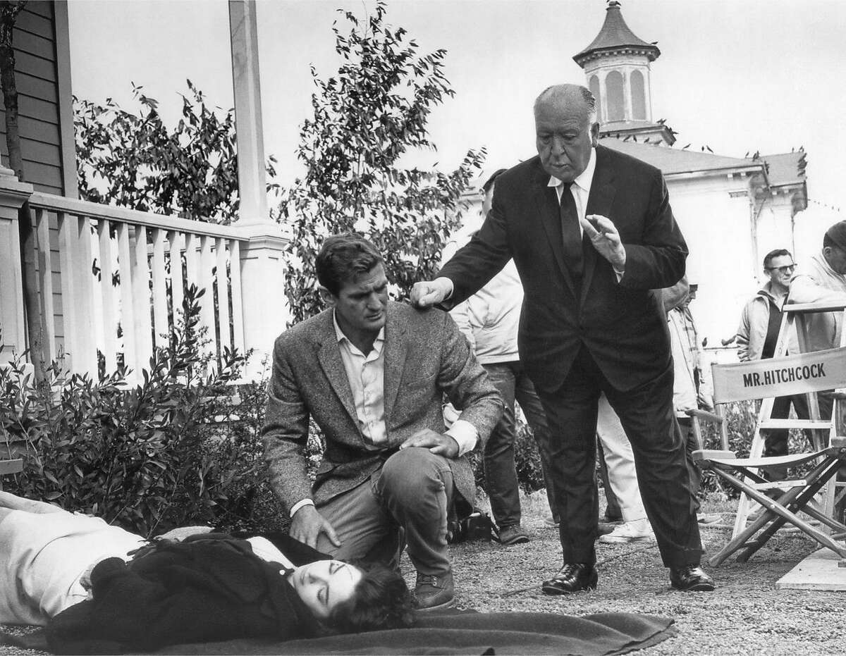 """Alfred Hitchcock directs as Rod Taylor kneels by Suzanne Pleshette on the set of """"The Birds."""""""