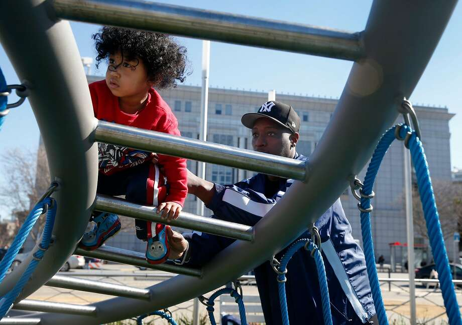 Clinton Turner, 2, gets a helping hand from his dad Daymian while exploring the $10 million playgrounds that opened near City Hall. The Turners live three blocks from the playgrounds. Photo: Paul Chinn, The Chronicle
