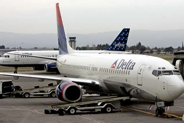 A Delta Air Lines plane takes on passengers as a JetBlue plane prepares to take off at San Jose Airport in San Jose, Calif., Thursday, July 21, 2005. Delta Air Lines Inc., the nation's third-largest carrier, said Thursday its second-quarter loss narrowed significantly compared to a year ago, but said persistently high fuel prices have limited the impact of solid gains in revenue. JetBlue Airways Corp. shares slumped more than 7 percent Thursday after the low-cost carrier said its second-quarter profit dropped 43 percent from soaring fuel costs that offset an upswing in passenger traffic and operating revenue. (AP Photo/Paul Sakiuma)