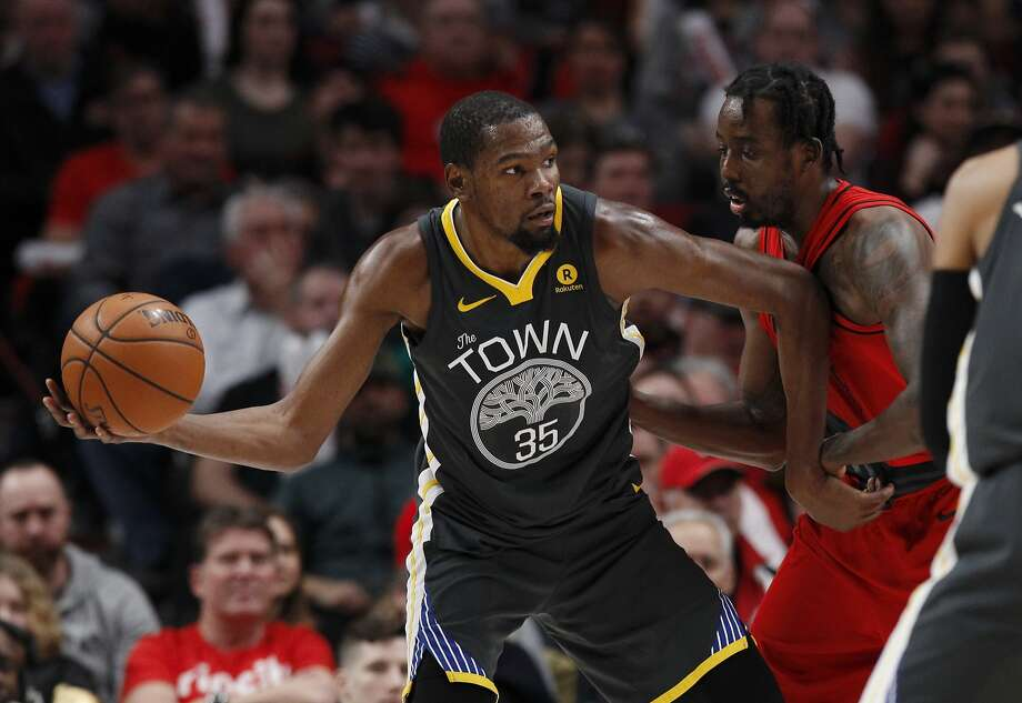 Golden State Warriors forward Kevin Durant, left, looks to pass against Portland Trail Blazers forward Al-Farouq Aminu during the second half of an NBA basketball game in Portland, Ore., Wednesday, Feb. 14, 2018. The Trail Blazers won 123-117.(AP Photo/Steve Dipaola) Photo: Steve Dipaola, Associated Press