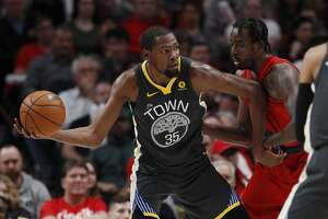 Golden State Warriors forward Kevin Durant, left, looks to pass against Portland Trail Blazers forward Al-Farouq Aminu during the second half of an NBA basketball game in Portland, Ore., Wednesday, Feb. 14, 2018. The Trail Blazers won 123-117.(AP Photo/Steve Dipaola)