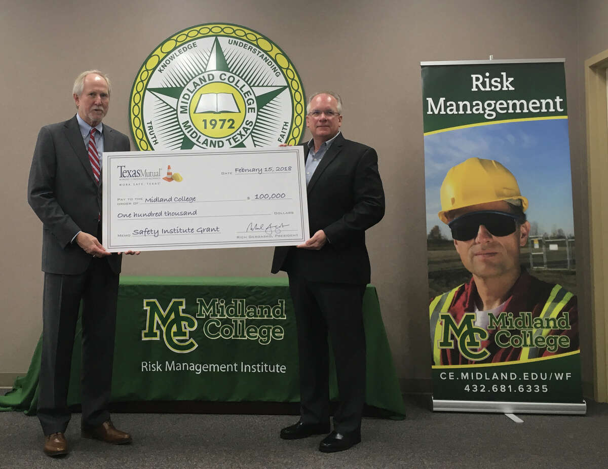 Scott Bain, Texas Mutual Insurance regional manager, right, presents Midland College President Steve Thomas with a check for $100,000 to fund the school's Risk Management Institute on Thursday, Feb. 15, 2018. A ceremony was held at MC's Advanced Technology Center.