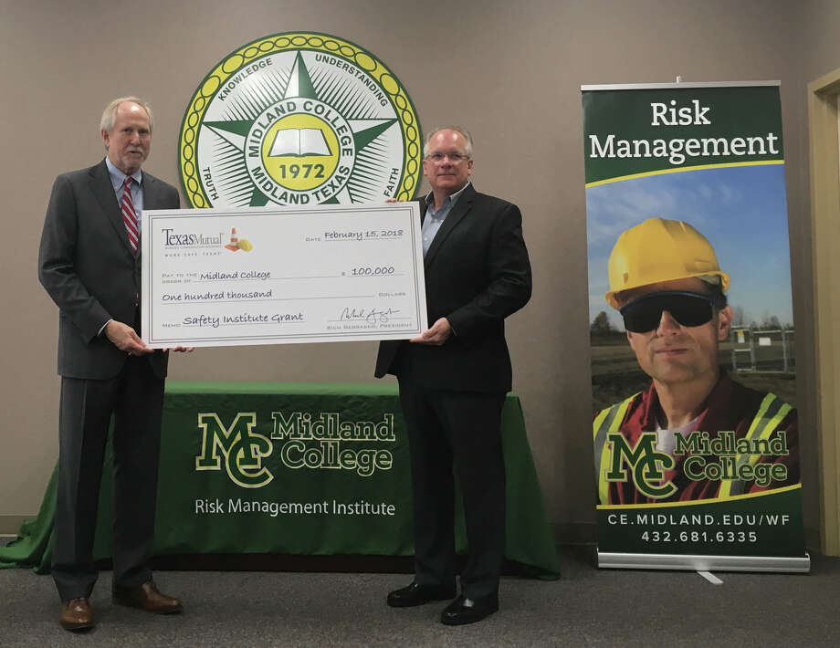 Scott Bain, Texas Mutual Insurance regional manager, right, presents Midland College President Steve Thomas with a check for $100,000 to fund the school's Risk Management Institute on Thursday, Feb. 15, 2018. A ceremony was held at MC's Advanced Technology Center. Photo: Trevor Hawes/Reporter-Telegram
