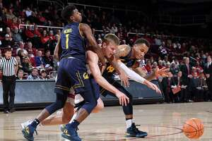 Stanford, CA - December 30, 2017:  Cal's Darius McNeill (#1) and Don Coleman (#14) hold off  Stanford's Michael Humphrey (#10) during NCAA Pac-12 Men's Basketball game at Maples Pavilion in Stanford, California.