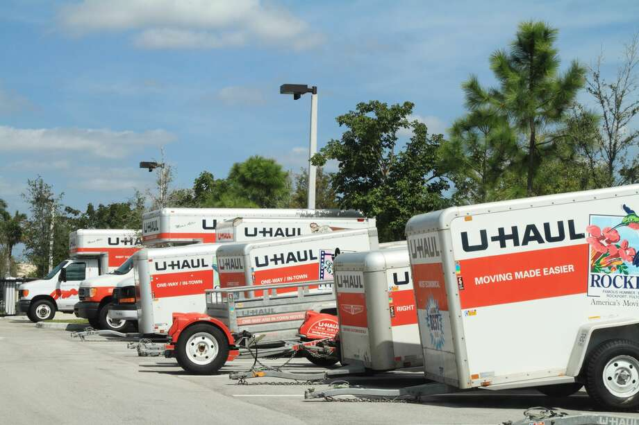 A row of U-Haul trucks and trailers are parked in a storage lot. Photo: NoDerog/Getty Images