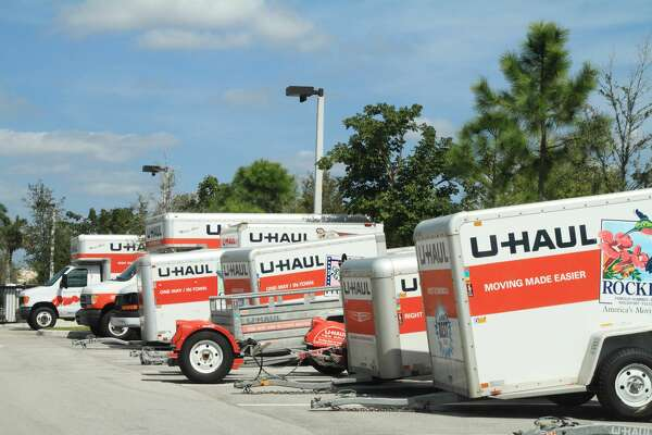 A row of U-Haul trucks and trailers are parked in a storage lot.