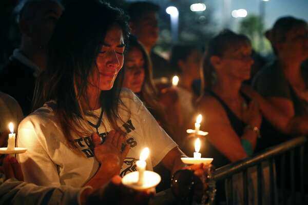 Lavinia Zapata, whose son is a student at Marjory Stoneman Douglas High School, cries during a candlelight vigil for the victims of the Wednesday shooting at the school, in Parkland, Fla., Thursday, Feb. 15, 2018. Nikolas Cruz, a former student, was charged with 17 counts of premeditated murder on Thursday. (AP Photo/Gerald Herbert)