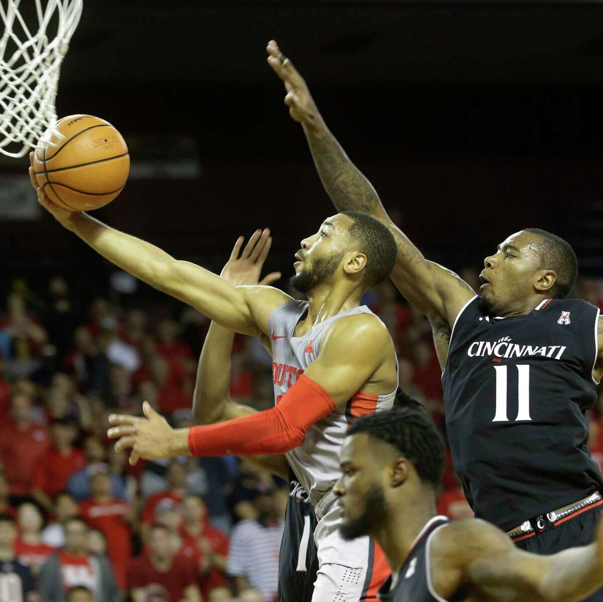 University of Houston Galen Robinson Jr. shoots past and the University of Cincinnati Gary Clark during the first half of game at Texas Southern University Thursday, Feb. 15, 2018, in Houston.