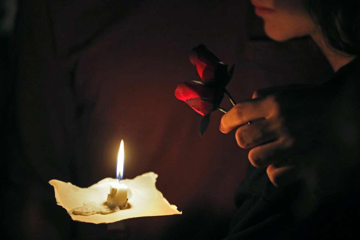 A young man and woman hold two roses and a candle during a candlelight vigil for the victims of the Wednesday shooting at Marjory Stoneman Douglas High School, in Parkland, Fla., Thursday, Feb. 15, 2018. Nikolas Cruz, a former student, was charged with 17 counts of premeditated murder on Thursday. (AP Photo/Gerald Herbert)
