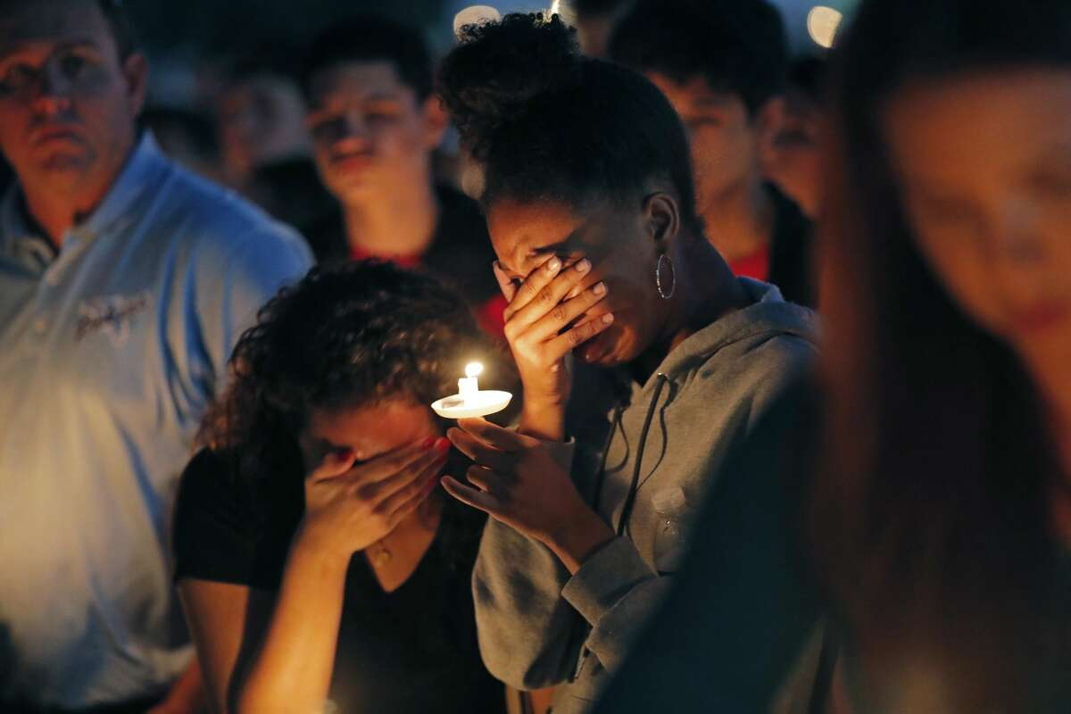 Kashiya Biggs, 17, facing left, a student at Marjory Stoneman Douglas High School, weeps with her friend Lex Reynoso, 16, as the names of deceased victims are read, during a candlelight vigil for the victims of the Wednesday shooting at the school, in Parkland, Fla., Thursday, Feb. 15, 2018. Nikolas Cruz, a former student, was charged with 17 counts of premeditated murder on Thursday. (AP Photo/Gerald Herbert)
