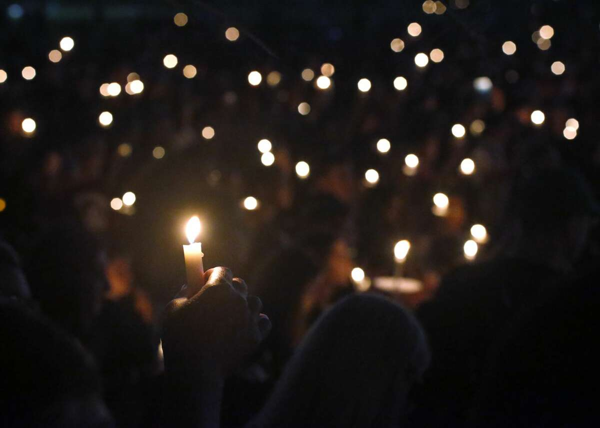Attendees hold up their candles at a candlelight vigil for the victims of the shooting at Marjory Stoneman Douglas High School, Thursday, Feb. 15, 2018, in Parkland, Fla. The teenager accused of using a semi-automatic rifle to kill 17 people and injuring others at a Florida high school confessed to carrying out one of the nation's deadliest school shootings and concealing extra ammunition in his backpack, according to a sheriff's department report released Thursday. (AP Photo/Wilfredo Lee)
