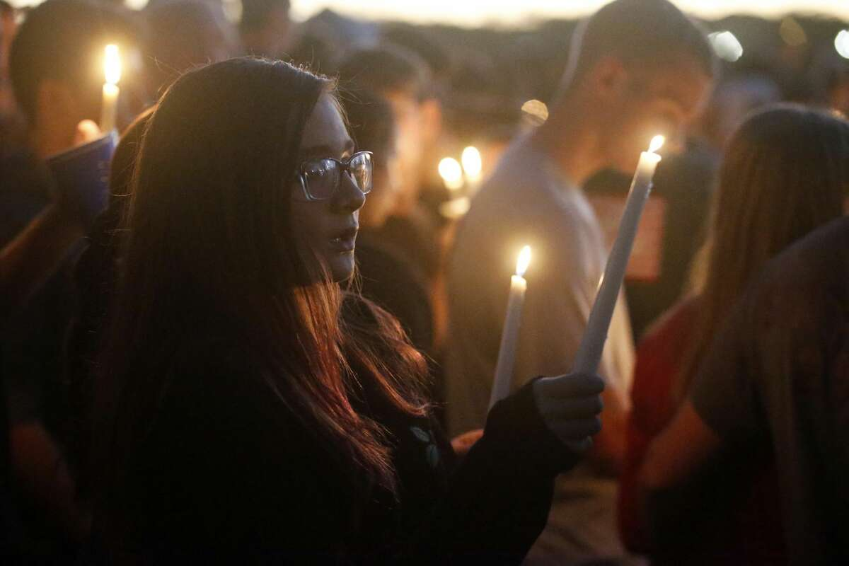 Attendees raise their candles at a candlelight vigil for the victims of the shooting at Marjory Stoneman Douglas High School, Thursday, Feb. 15, 2018, in Parkland, Fla. The teenager accused of using a semi-automatic rifle to kill 13 students and four employees at a Florida high school confessed to carrying out one of the nation's deadliest school shootings and concealing extra ammunition in his backpack, according to a sheriff's department report released Thursday. (AP Photo/Wilfredo Lee)