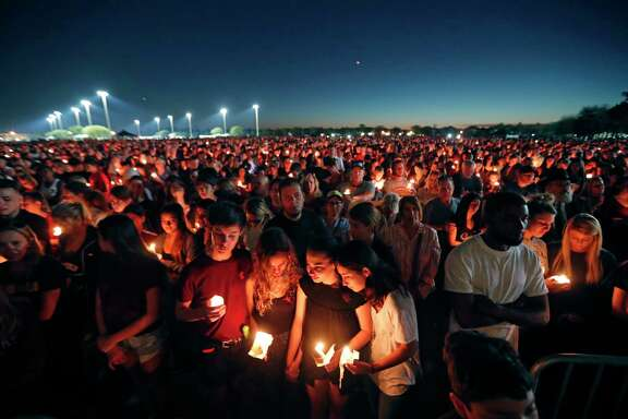 People attend a candlelight vigil Thursday for the victims of the Wednesday shooting at Marjory Stoneman Douglas High School, in Parkland, Fla.. Among the dead were teachers and students: a popular football coach, a soccer player and a trombonist in the band.