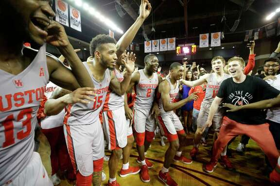 University of Houston players celebrate with fans after posting a big victory over fifth-ranked Cincinnati at H&PE Arena on Thursday night.