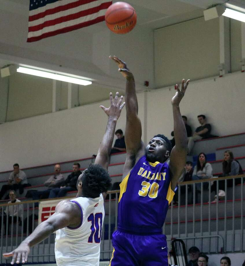 UAlbany forward Travis Charles makes a 3-pointer as UMass-Lowell guard Jahad Thomas defends during their game Thursday, Feb. 15, 2018. (George DeLuca / Special to the Times Union)