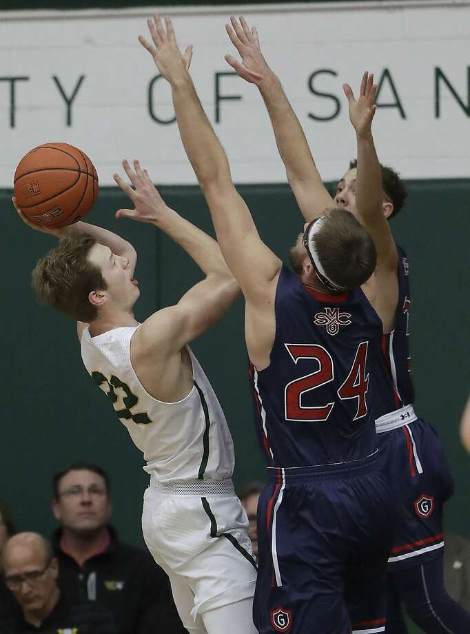 San Francisco forward Chase Foster, left, shoots against Saint Mary's forward Calvin Hermanson (24) and guard Jordan Ford during the first half of an NCAA college basketball game in San Francisco, Thursday, Feb. 15, 2018. (AP Photo/Jeff Chiu) Photo: Jeff Chiu, Associated Press