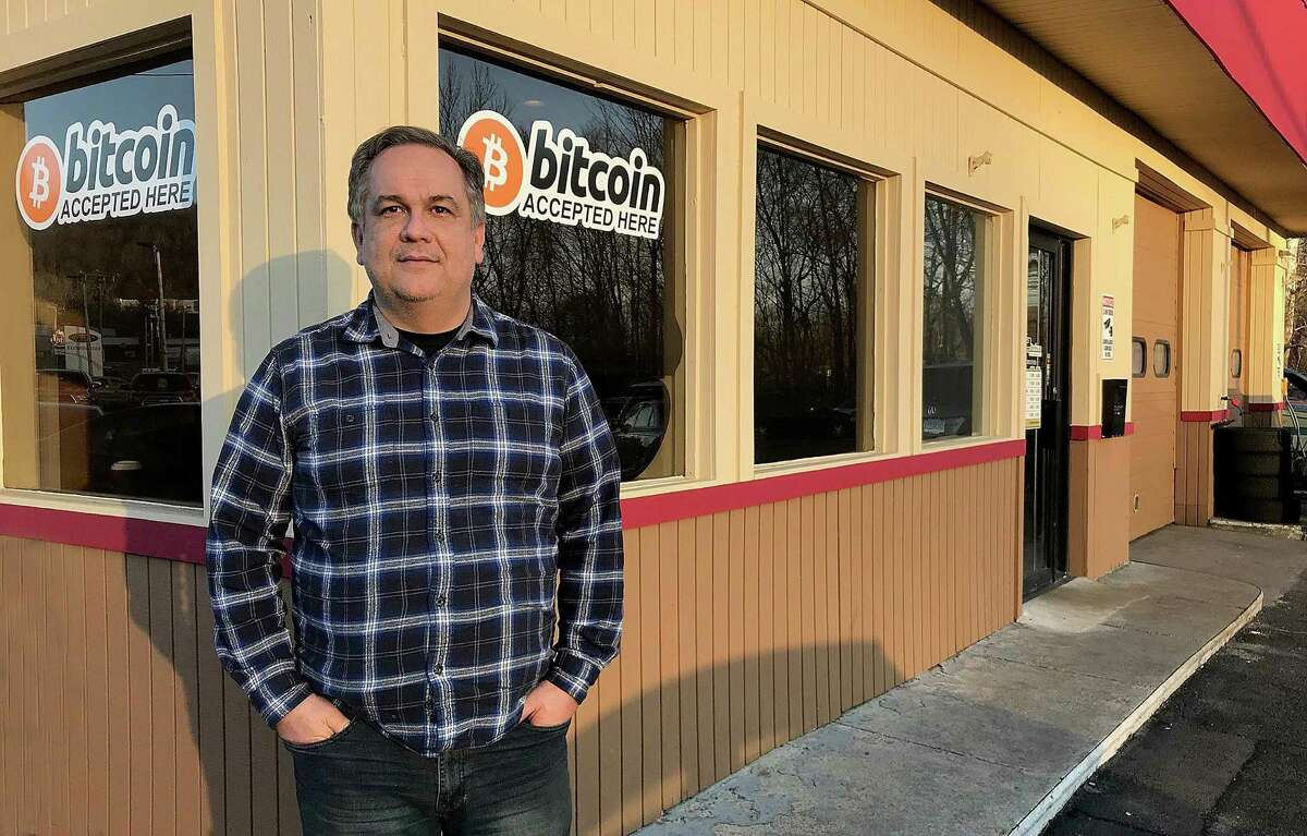 """John Fieschi, who owns EZ2Ddrive with his wife Eda, stands by the """"bitcoin accepted here"""" sign at his used car dealership and garage in Danbury, Conn., on Tuesday, Feb. 6, 2018."""