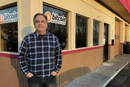 "John Fieschi, who owns EZ2Ddrive with his wife Eda, stands by the ""bitcoin accepted here"" sign at his used car dealership and garage in Danbury, Conn., on Tuesday, Feb. 6, 2018."