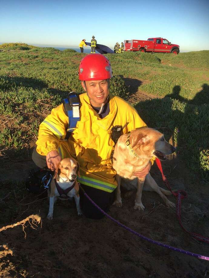 Firefighter paramedic Art Julaton poses with the two dogs he saved Friday. Photo: SFFD / / San Francisco Fire Department