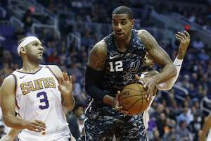 San Antonio Spurs forward LaMarcus Aldridge (12) grabs a rebound in front of Phoenix Suns forward Jared Dudley (3) during the first half of an NBA basketball game Wednesday, Feb. 7, 2018, in Phoenix. The Spurs defeated the Suns 129-81. (AP Photo/Ross D. Franklin)