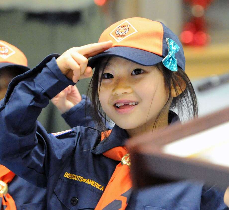 New Cub Scout Coco Lee, 8, salutes during a Pack 23 induction ceremony in Greenwich on Feb. 8. Photo: Bob Luckey Jr. / Hearst Connecticut Media / Greenwich Time