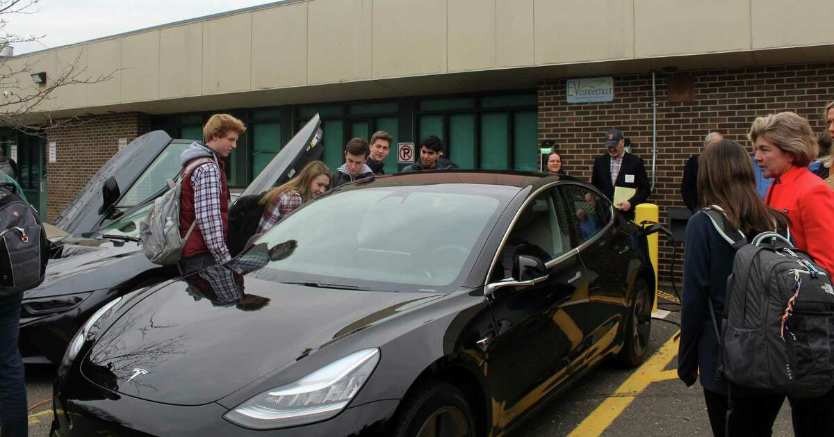 Students at Staples High School look at Westport resident Bruck Becker's Tesla Model 3 at an event showcasing his new vehicle on Wednesday.