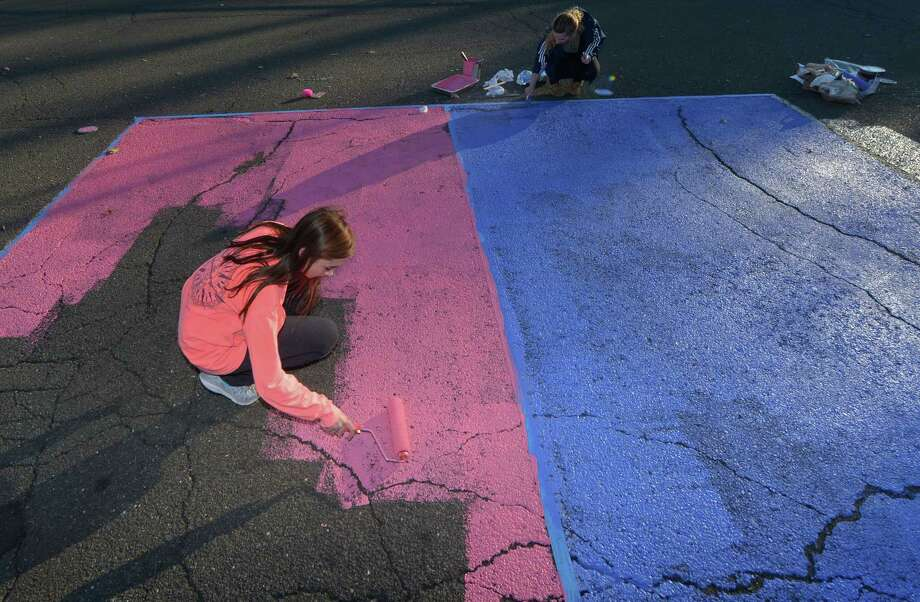 Seniors at Brien McMahon High School including Chrissy Kirst paint their parking spaces Friday, Nov. 17, 2017, at the school. To celebrate all students and to build a culture of inclusiveness, Brien McMahon High School creates an annual lip dub video. Photo: Erik Trautmann / Hearst Connecticut Media / Norwalk Hour