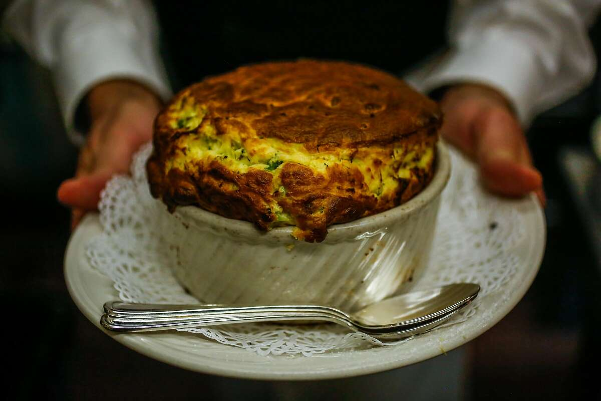 Server Matthew Weimer holds a freshly made souffle at Cafe Jacqueline in San Francisco, California, on Wednesday, Jan. 31, 2018.