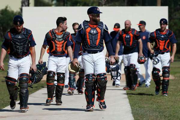 Houston Astros catchers led by Brian McCann (16) walk back from a practice wall during spring training at The Ballpark of the Palm Beaches, Friday, Feb. 16, 2018, in West Palm Beach .