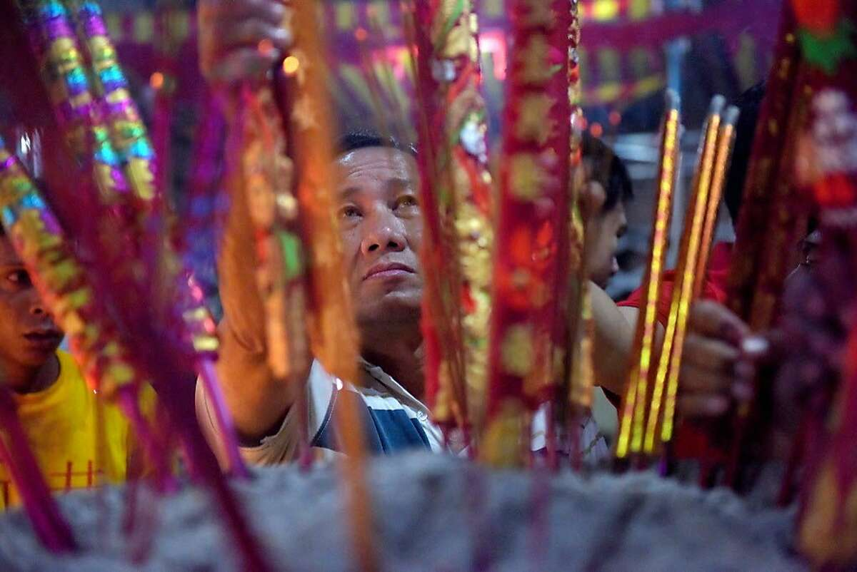 A Cambodian-Chinese man places a stick of incense into an urn at a temple to mark the start of the Lunar New Year in Kandal on February 16, 2018. (AFP PHOTO / TANG CHHIN SothyTANG CHHIN SOTHY/AFP/Getty Images)