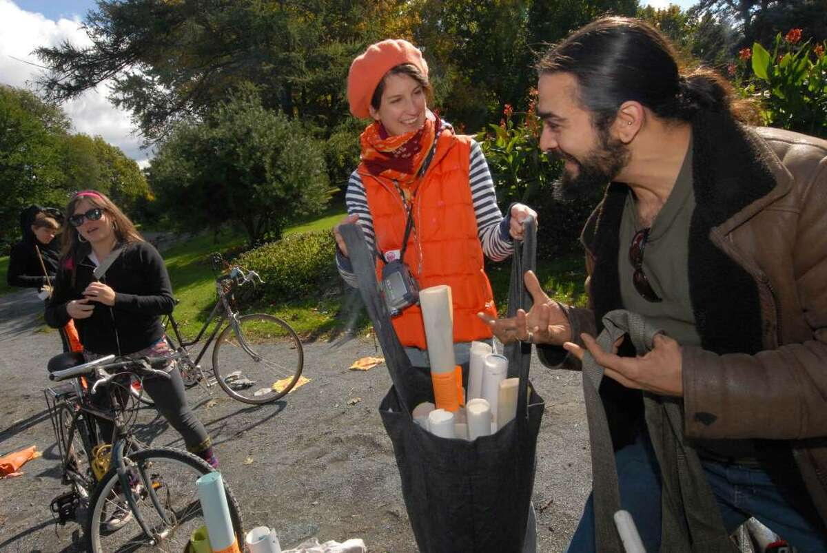 Sina Hickey , center, and Samson Contompasis,right, part of PaperGirl, a performance art/guerrilla art project in which they and others ride bikes and hand out rolled-up original art on the streets of Albany, organize at Washington Park. (Michael P. Farrell / Times Union )