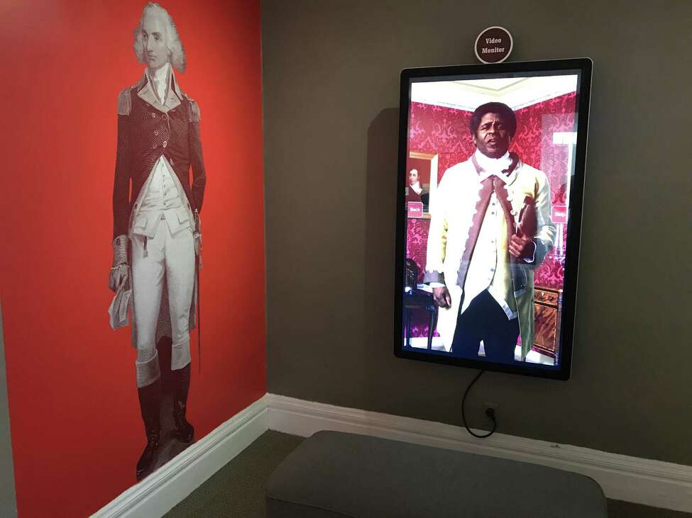 Part of the exhibit at the Schuyler Mansion visitor center, where Philip Schuyler, at left, shares a room with enslaved butler Prince, portrayed by an actor in a video at right. (photo by Amy Biancolli)