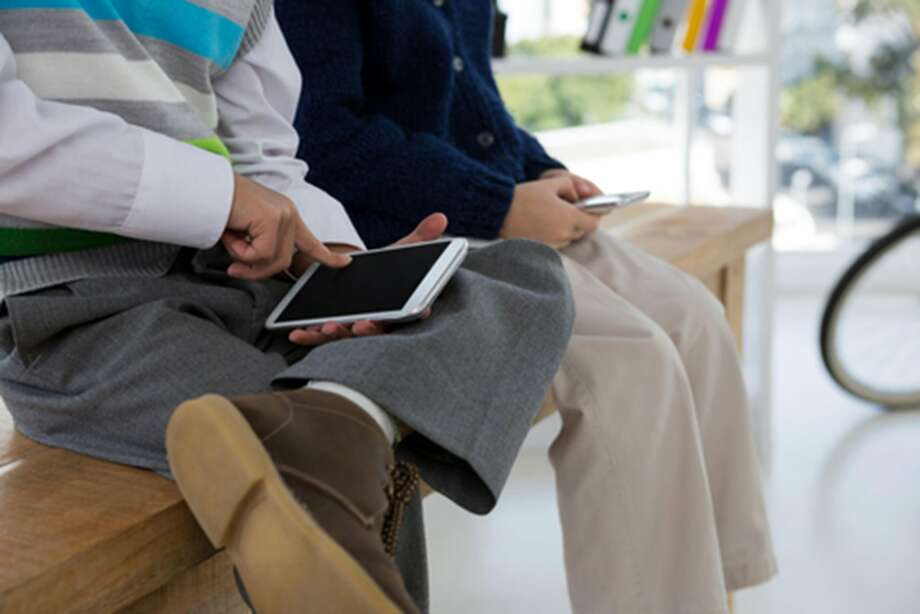 Kids as business executives using smartphone while sitting on table Photo: Dreamstime/TNS, TNS