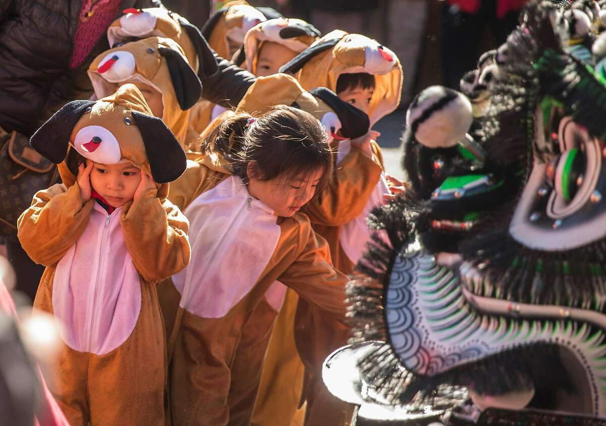 Local school children dressed as dogs marking the Year of the Dog exit Portsmouth Square after performing during the kick-off event for Chinese New Year in Chinatown Friday, Feb. 16, 2018 in San Francisco, Calif.
