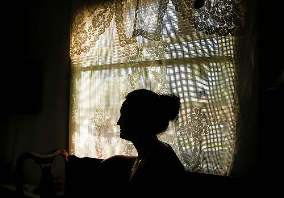 The mother of a girl, who lived at Mary Graham Children's Shelter and was jailed on property crime charges, sits in her home. Photo: Jessica Christian, The Chronicle