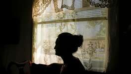 The mother of a 14-year-old girl who formerly resided at Mary Graham Children's Shelter is seen silhouetted in the window of her home Thursday, Feb. 15, 2018 in Stockton, Calif.