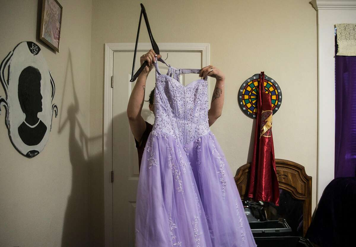 The mother of a 14-year-old girl who formerly resided at Mary Graham Children's Shelter holds up her daughter's favorite dress in her daughter's bedroom Thursday, Feb. 15, 2018 in Stockton, Calif.