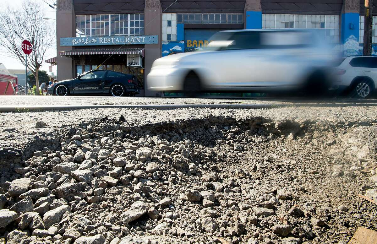 A drivers navigates a damaged section of 18th St. in Oakland, Calif., on Saturday, Feb. 3, 2018.