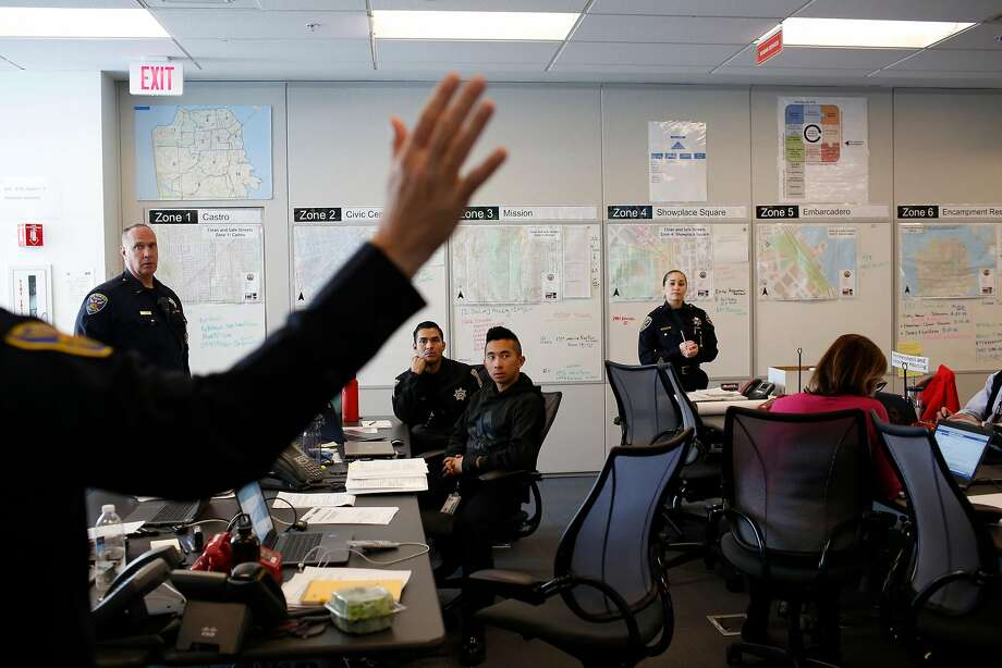 Police Cmdr. David Lazar (raising hand at left) talks in a multi-department meeting at the city's command center on homeless issues in the Department of Emergency Management building. Photo: Lea Suzuki, The Chronicle