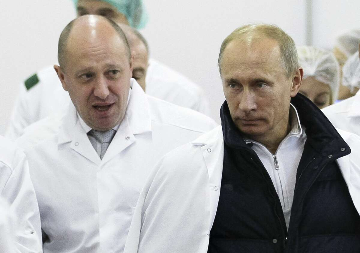 FILE - In this Monday, Sept. 20, 2010 file photo, businessman Yevgeny Prigozhin, left, shows Russian President Vladimir Putin, around his factory which produces school meals, outside St. Petersburg, Russia. Indicted for alleged U.S. election interference, Prigozhin is a wealthy Russian entrepreneur from St. Petersburg who's been dubbed