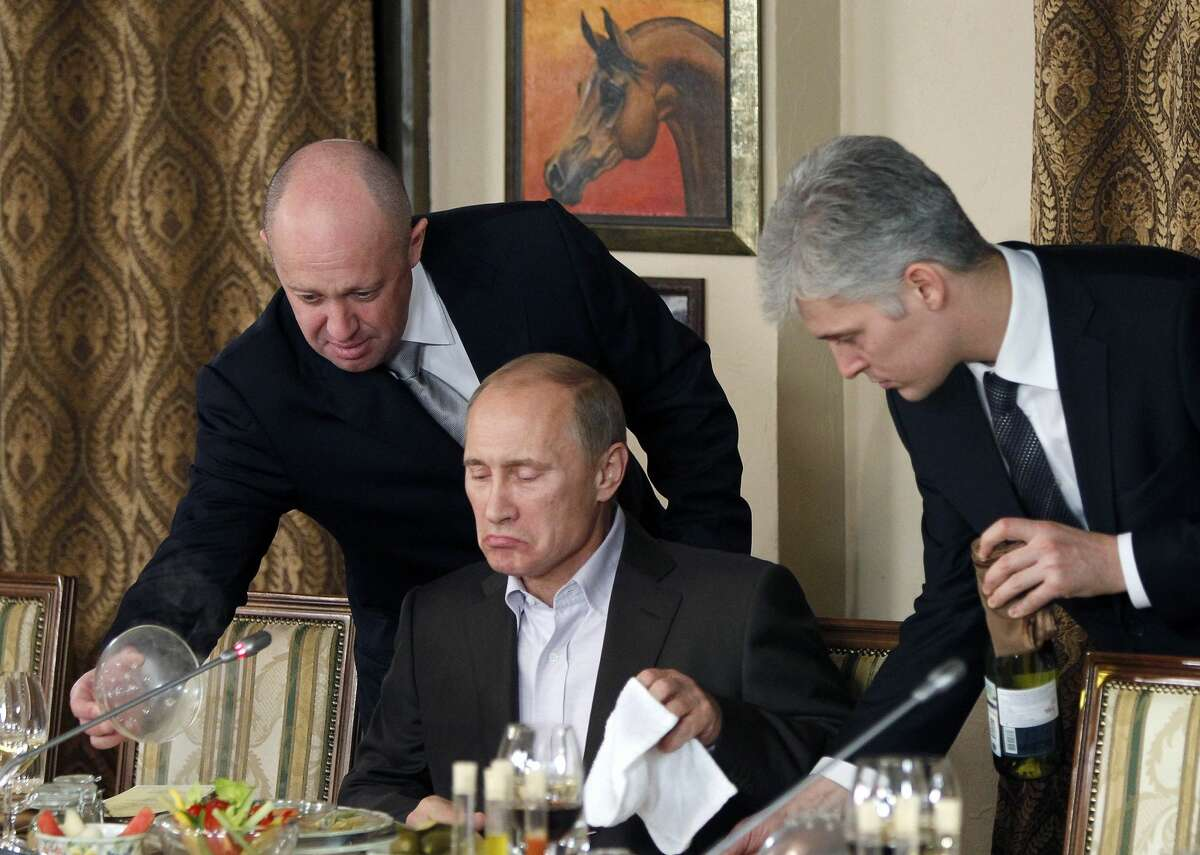 FILE - In this Friday, Nov. 11, 2011 file photo, businessman Yevgeny Prigozhin, left, serves food to Russian Prime Minister Vladimir Putin, center, during dinner at Prigozhin's restaurant outside Moscow, Russia. Indicted for alleged U.S. election interference, Prigozhin is a wealthy Russian entrepreneur from St. Petersburg who's been dubbed