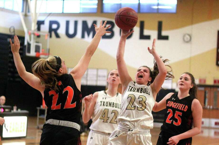 Trumbull's Julie Keckler attempts a shot as Ridgefield's Caroline Curnal defends during girls basketball action in Trumbull, Conn., on Saturday Jan. 20, 2018. Photo: Christian Abraham / Hearst Connecticut Media / Connecticut Post