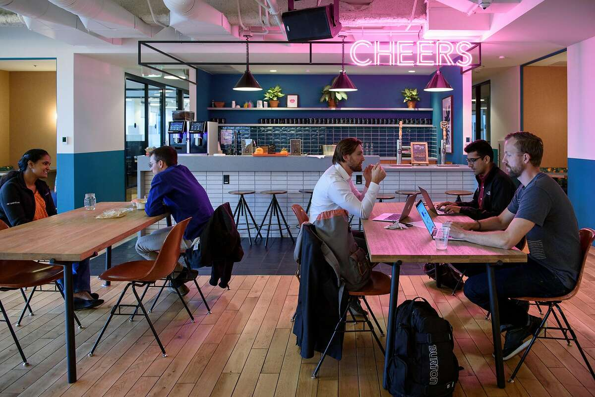 A bar area is seen in the background as WeWork members work in a common room at the Embarcadero WeWork offices in San Francisco, Calif, on Thursday October 19, 2017.