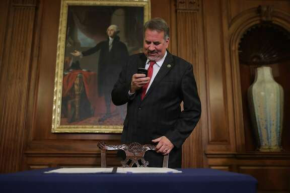 WASHINGTON, DC - JANUARY 07:  U.S. Rep. Doug LaMalfa (R-CA) uses his Blackberry to photograph legislation to repeal the Affordable Care Act, also known as Obamacare, and to cut off federal funding of Planned Parenthood that had just been signed by Speaker of the House Paul Ryan (R-WI) following an enrollment ceremony in the Rayburn Room at the U.S. Capitol January 7, 2016 in Washington, DC. President Barack Obama has promised to veto the bill.  (Photo by Chip Somodevilla/Getty Images)