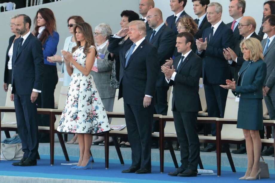 Flanked by first lady Melania Trump, left, and French President Emmanuel Macron, right, President Donald Trump salutes U.S. troops during the annual Bastille Day military parade in Paris. This is the parade that inspired Trump to seek a similar event in Washington, D.C. Photo: JOEL SAGET /AFP /Getty Images / AFP or licensors